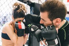 Mma training. Couple making sparring in the mma cage. concept about fighting, fitness and sport Royalty Free Stock Photo