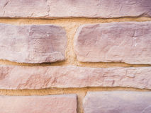 Mmasonry of stoun wall, background. A wall from an artificial gray stone facade with rough fractured surfaces Royalty Free Stock Photography