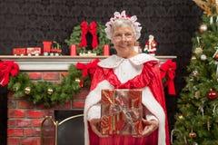 Mme Clause tenant un cadeau de Noël photographie stock libre de droits