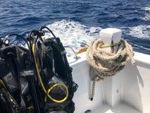 Mnóstwo czarny nurkowy kostium z wężami elastycznymi i nurkowe kurtki wieszamy na stojaku i ciężka arkana na szybkiej łodzi, wysy zdjęcie stock