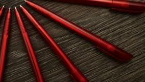 Mnóstwo czerwoni pióra ruszają się w okręgu na czarnym drewnianym tle Pojęcia biuro lub szkoła, wiedza dzień pierwszy Wrzesień zbiory wideo