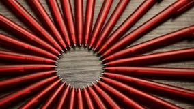 Mnóstwo czerwoni pióra ruszają się w okręgu na czarnym drewnianym tle Pojęcia biuro lub szkoła, wiedza dzień pierwszy Wrzesień zbiory