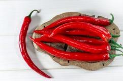 Mnóstwo czerwony pepers chili kłama na owalnej Brown desce która stoi na białym drewno stole, zdjęcie royalty free