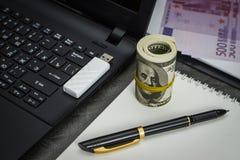 Mnóstwo dolary na notatniku blisko laptopu z błysną przejażdżkę obraz stock