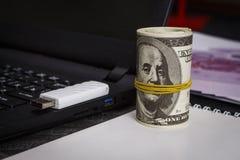 Mnóstwo dolary na notatniku blisko laptopu z błysną przejażdżkę zdjęcie royalty free