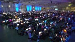 Mnóstwo gamers bawić się na grach komputerowych w wielkiej hali zbiory