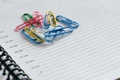 Mnóstwo kolorowe zszywki kłama na pustej stronie notatnik Obrazy Royalty Free