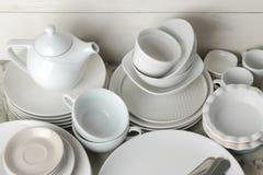 Mnóstwo różni naczynia łomotanie na lekkim betonowym tle naczynia dla słuzyć stół różnorodni talerze, puchary i cu, zdjęcie stock