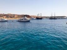 Mnóstwo różnorodny silnika i żeglowanie statków stojak na quay w porcie na tle błękitny solankowy morze i nawadnia i brąz zdjęcia royalty free