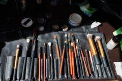 Mnóstwo różny kosmetyczny makeup szczotkuje lying on the beach w kosmetycznej torbie Wiele inni kosmetyczni produkty są na stole Zdjęcia Stock