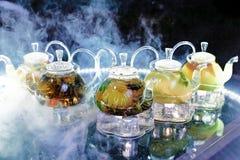 Mnóstwo szklani teapots z herbatą na stole w dymu Obraz Royalty Free