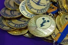 Mnóstwo złoci medale z żółtymi faborkami na srebnej tacy, nagrody mistrzowie, sporta ac zdjęcia stock
