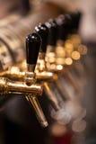 Mnóstwo Złoci piw klepnięcia przy barem Zdjęcie Royalty Free