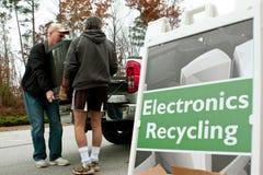 Män bär TV för att tappa av på återvinninghändelsen Arkivfoto