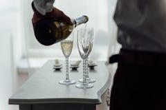 Män häller champagne in i exponeringsglas Royaltyfri Fotografi