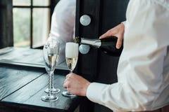 Män häller champagne in i exponeringsglas Arkivbilder