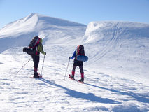 Män i snöskor går i bergen Arkivfoto