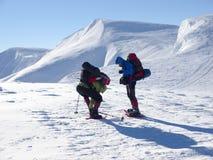 Män i snöskor går i bergen Arkivbild