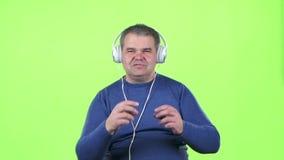 Mn lyssnar till musik på hörlurar grön skärm långsam rörelse lager videofilmer