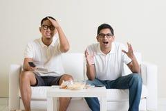 Män som hemma håller ögonen på fotbollsmatchen på tv Royaltyfri Foto