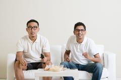 Män som tillsammans håller ögonen på fotbollleken på tv Arkivfoton