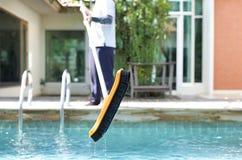 Mna gör ren en simbassäng med en borste Arkivbilder