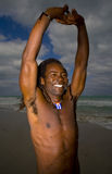 Mna streching in cuba. Smiling black man etiring on the beach near the water Royalty Free Stock Images