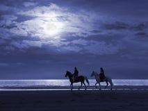 månbelysta strandhorseriders Arkivbilder