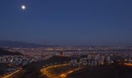 Måne och staden - en sikt från Izmir Arkivfoton