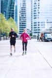 Mång--person som tillhör en etnisk minoritet par som joggar i stads- inställning Arkivbilder
