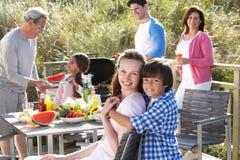 Mång- utvecklingsfamilj som har den utomhus- grillfesten Arkivbild