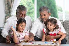Mång- utvecklingsfamilj som spelar lekar Arkivbild