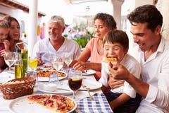 Mång- utvecklingsfamilj som äter mål på den utomhus- restaurangen Arkivfoto