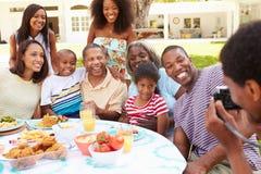Mång- utvecklingsfamilj som tillsammans tycker om mål i trädgård Arkivfoton