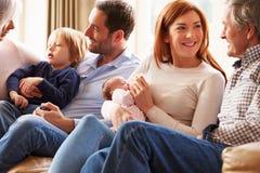 Mång- utvecklingsfamiljsammanträde på Sofa With Newborn Baby Arkivbilder