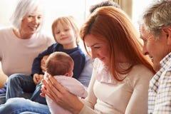 Mång- utvecklingsfamiljsammanträde på Sofa With Newborn Baby Royaltyfria Bilder