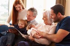Mång- utvecklingsfamiljsammanträde på Sofa With Newborn Baby Royaltyfri Bild
