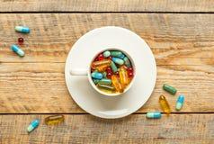 Många färgrika preventivpillerar i kopp wodden på tabellen Arkivbild