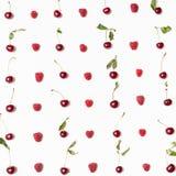 Många hallon och körsbär som är ordnade på fyrkant Arkivfoton