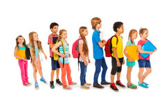 Många lyckliga ungar i en linje till skolan Arkivbild