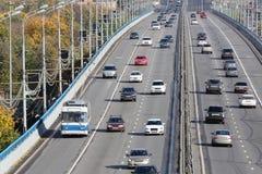 Många moderna bilar går på bron på den soliga dagen Royaltyfria Foton