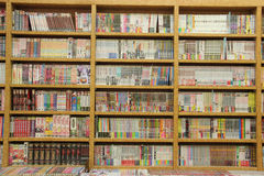 Många olika böcker på träbokhyllor Royaltyfri Foto
