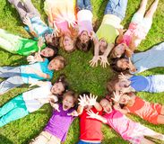 Många ungar med lyftande händer på gräs Fotografering för Bildbyråer
