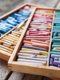 Mångfärgade yrkesmässiga konstnärliga pastellfärgade färgpennor i öppen ask Arkivfoto