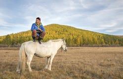 Mngolian年轻人坐一个白马 库存照片