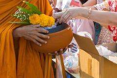 Mnich buddyjski podczas gdy stojak czeka ludzi z rzędu stawia ryż ofertę Obrazy Royalty Free