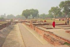 Mnich buddyjski w czerwieni sukni odprowadzenia past rujnował świątynię w świętym miejscu z zielonymi drzewami Obraz Stock