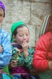 Mniejszości etnicznych dzieci jedzą trzciny cukrowa, przy starym Dong Van rynkiem Zdjęcie Royalty Free