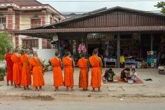 Mnisi buddyjscy zbiera datki w ranku w Vang Vieng, Laos zdjęcie royalty free