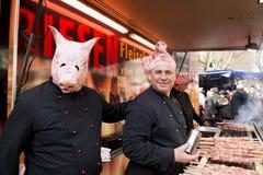 Männer auf dem Grill kostümiert als Schweine Stockbilder